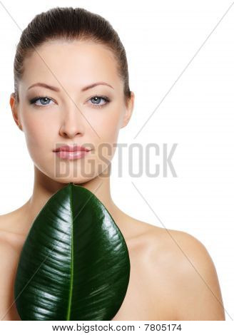 Beautiful Fresh Woman's Face With Large Green Leaf
