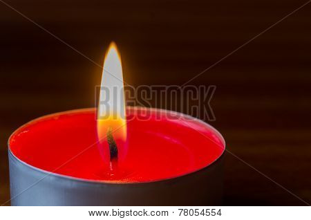 Dark glowing red tea light on wooden table