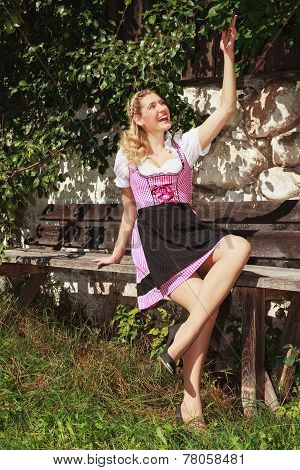 Cheerful woman in dirndl on a bench