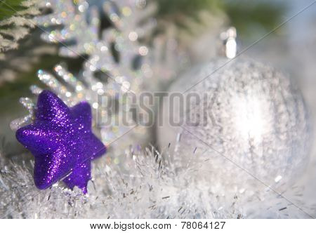 Decorative violet star, snowflake and a silvery Christmas ball out of focus
