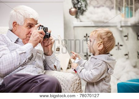 Senior man taking photo of his toddler grandson