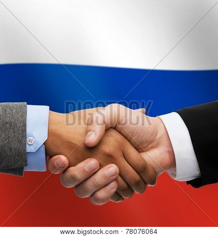 partnership, politics, gesture and people concept - close up of handshake over russian national flag background
