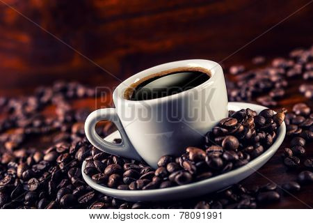 Cup of black coffee and spilled coffee beans.