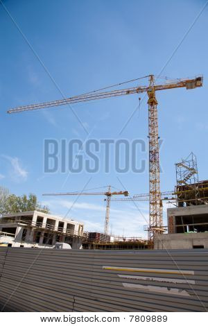 Two Construction Cranes Working On A Building Site