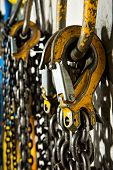 stock photo of pulley  - Several large industrial weathered yellow hooks attached to chain and a pulley - JPG
