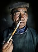 picture of mongolian  - Mongolian man in traditional dress smoking a pipe - JPG