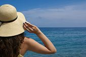image of beach hat  - Young beautiful woman in summer hat relaxing on the beach - JPG