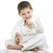 picture of karate kid  - Little karate kid sitting legs crossed pointing forward - JPG