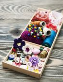 picture of handicrafts  - thread and material for handicrafts in box on a wooden background - JPG