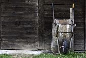 picture of wheelbarrow  - Wheelbarrow to rest leaning against a wooden door of a tool shed - JPG
