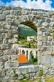 picture of aqueduct  - The view on the winding aqueduct through the small window in the fortress wall Stari Bar Montenegro - JPG