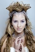 stock photo of snow queen  - beauty young snow queen in fairy flashes with hair crown on her head close up - JPG