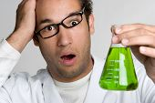 stock photo of mad scientist  - Crazy scientist holding green liquid in test tube - JPG