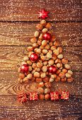 pic of hazelnut tree  - Christmas tree made of hazelnuts with red baubles and gifts on wooden background - JPG