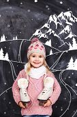 picture of little girls photo-models  - Little girl with skates on his neck standing near the mountains - JPG