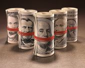 pic of gag  - Money rolls with elastic gagging the mouths of the symbols of United States currency - JPG