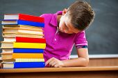 picture of schoolboys  - Adorable schoolboy with stack of books in classroom - JPG