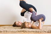 stock photo of physical education  - Young pregnant woman with little daughter doing yoga exercises
