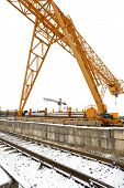 pic of railroad yard  - gantry cranes over railroad in metal pipe outdoor warehouse - JPG