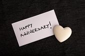picture of amour  - Happy anniversary handwritten on a white card with a cream colored heart lying on a black background for an anniversary greeting - JPG
