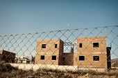 pic of abandoned house  - Fenced building site with abandoned unfinished houses - JPG