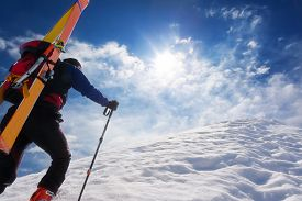 stock photo of winter sport  -  Ski mountaineer walking up along a steep snowy ridge with the skis in the backpack - JPG