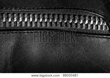 Black leather texture with metal zipper, closeup