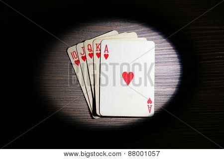 Playing cards in light on wooden table, top view