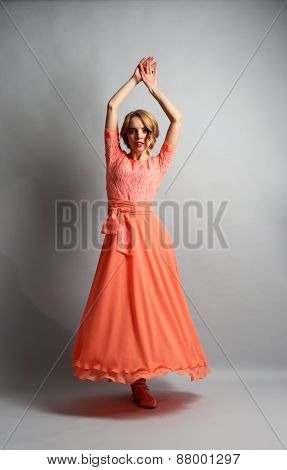 Beautiful young woman in color dress posing on light background