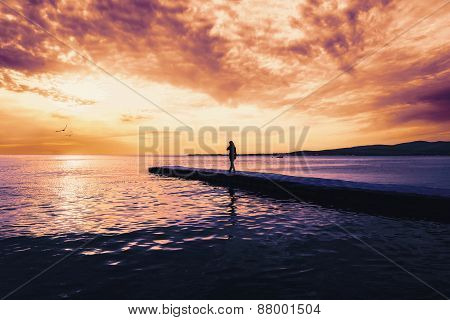 Woman Walking On Pier At Sunset
