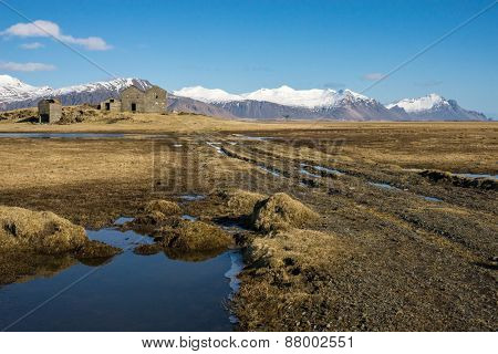 An abandoned farm-house sits on a wide open grass field with the background formed by the snow-capped mountains. The rivers and lakes are formed by the melting ice from the mountains.