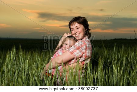 happy mother and child in green field at sunset