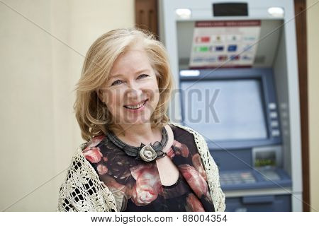 Happy Mature blonde woman near automated teller machine in shop