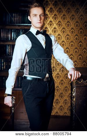 Young handsome man in evening suit stands by the fireplace in a room with classic vintage interior. Fashion.
