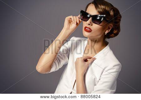 Close-up portrait of a gorgeous young woman wearing retro glasses. Beauty, fashion. Make-up. Optics, eyewear.