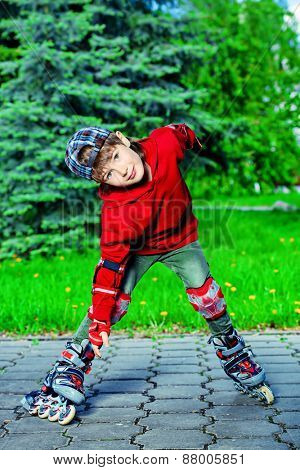 Cool 7 year old boy rollerblades on the street. Childhood. Summertime.