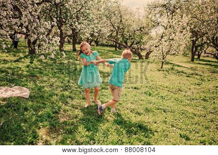 happy brother and sister dancing in spring apple garden