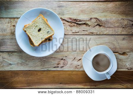 Hot Coffee And Raisin Bread On Wood Table