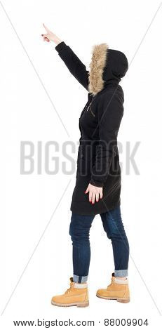 Back view of  pointing young women in parka. Young girl gesture. Rear view people collection.  backside view of person.  Isolated over white background.