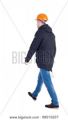 Back view of goingWorker in a helmet. walking young engineer. Rear view people collection.  backside view of person.  Isolated over white background.