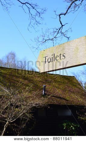 Rural wood finger post toilet sign