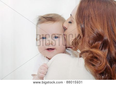 Caring Mother Kissing  Her Cute Happy Baby Boy