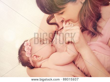 Caring Mother Kissing Fingers Of Her Cute Sleeping Baby Girl