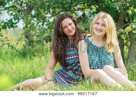 Portrait Of Friends Resting On Grass In Summer Garden
