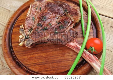 meat savory : roasted beef ribs served with green chives and cherry tomato over wood