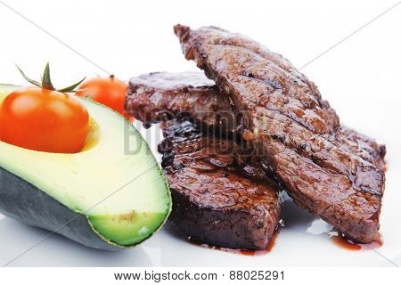 grilled beef fillet with avocado and tomatoes on white plate isolated over white background