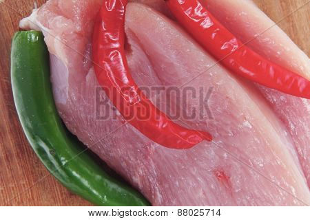 fresh raw turkey meat pieces on wooden cutting plate with red and green hot chili pepper isolated over white background