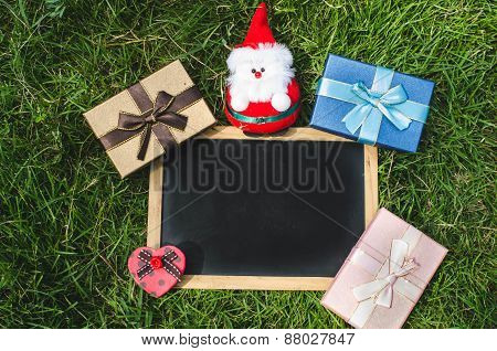 Blank Blackboard With Christmas Decoration On Green Grass.