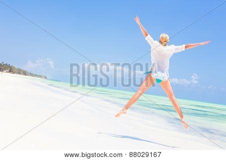 Beautiful Girl Jumping on Tropical Beach.