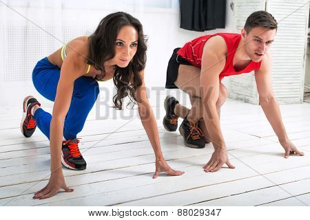 Beautiful girl and handsome guy in strat position for a run on the white wooden floor sports hall